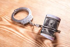 Metallic handcuffs with money. Financial crime concept royalty free stock photography