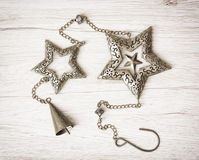 Metallic hanging stars and bell, Christmas decoration Royalty Free Stock Photos