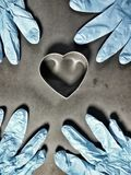Metallic heart and blue gloves Royalty Free Stock Image