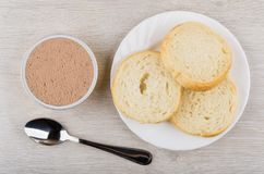 Metallic jar with liver pate, bread in plate and teaspoon. On wooden table. Top view Stock Images