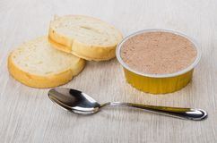 Metallic jar with liver pate, pieces of bread and teaspoon. On wooden table Royalty Free Stock Image