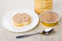 Metallic jar with liver pate, sandwich with pate in plate. And teaspoon on wooden table Royalty Free Stock Image