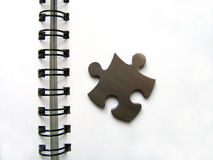 Metallic jigsaw on notebook. Metellic jigsaw piece on a white notebook with copy space royalty free stock images