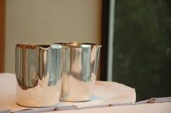 Metallic jugs on white table Stock Photo
