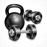 Metallic kettle bell and two dumbbells Royalty Free Stock Photo
