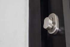 Metallic knob on white door Stock Photography