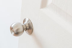 Metallic knob on white door Stock Image
