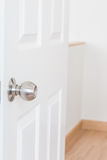 Metallic knob on white door Stock Photo