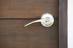 Metallic knob. On wooden door Stock Image