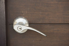 Metallic knob. On wooden door Stock Images
