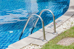 Metallic ladder for using entrance to swimming pool. Royalty Free Stock Photography