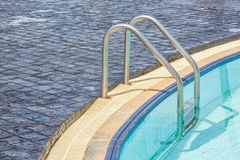 Metallic ladder for using entrance to swimming pool. Royalty Free Stock Image