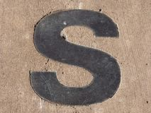 Metallic letter S embedded in pavement. A metallic letter S in pavement embedded in pavement Royalty Free Stock Images