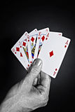 Metallic male hand holding a royal flush Royalty Free Stock Photos