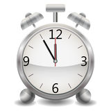A metallic mechanical realistic alarm clock, a clock showing at five minutes twelve, midnight or lunch Royalty Free Stock Image