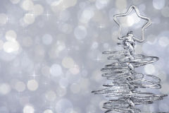 Metallic modern christmas tree on silver tint light bokeh background, xmas holiday. Concept Royalty Free Stock Photo