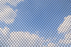 Metallic net. Blue sky with clouds behind metallic net Royalty Free Stock Photos