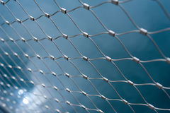 Metallic net with blue background Royalty Free Stock Image