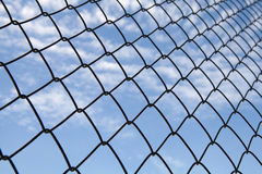 Metallic net with blue sky background Royalty Free Stock Photography