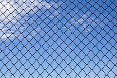 Metallic net with blue sky background. Close up metallic net with blue sky background Royalty Free Stock Images