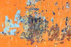 Metallic orange background with peeling paint and blue spots and stock photography