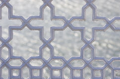 Metallic ornamental fence. Close up on cross, stars shape railing. Dark grey colour on water background. Stock Photography