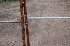 A metallic padlock and chain lock at fence door Stock Photo