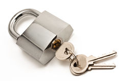 Metallic padlock with three keys in keyhole. Isolated on white Royalty Free Stock Images