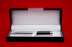 Metallic pen in a gift box against red background Royalty Free Stock Photo
