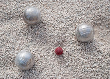 Metallic petanque balls and a small red jack Royalty Free Stock Images