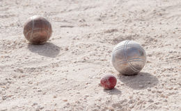 Metallic petanque balls and a small red jack Royalty Free Stock Photography