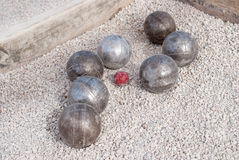 Metallic petanque balls and a small red jack Stock Photo