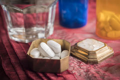 Metallic pillbox with white pills Stock Photography