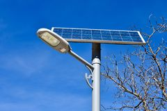metallic post in a street with a solar panel to generate renewable photovoltaic electricity. The solar panel produces electrical stock photography