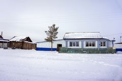 Metallic protection of the wooden house in a small Siberian village in the winter season. stock images