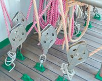 Metallic pulley block and ropes on the deck. Of an old sailboat ship royalty free stock photo
