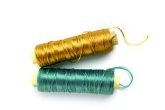 Metallic rayon thread line spool green and gold Stock Photo
