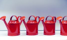 Metallic red watering cans for watering flowers and plants royalty free stock photography