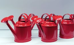 Metallic red watering cans for watering flowers and plants stock photo