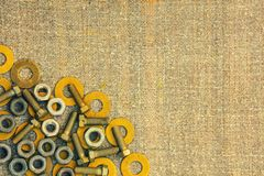 Metallic rings washers, nuts, screw, bolt on sackcloth. Abstract grunge background. Metallic rings washers, nuts, screw, bolt on sackcloth Royalty Free Stock Photography