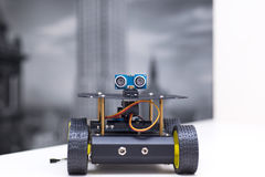 Metallic robot on four wheels stands on a white table Royalty Free Stock Photos