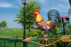 Metallic rooster wind cock vane brightly lit by the sun. Royalty Free Stock Photos