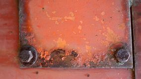 Metallic rust frame with bolts. Old orange piece of metal with some hexagonal bolts in it, welded square wit several paint damage and filled with rust Stock Photography