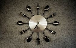 Metallic shining watch especially made for restaurants decoration with forks, spoons and knifes royalty free stock image
