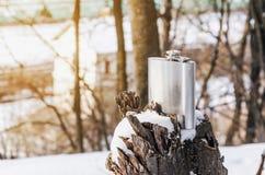Metallic shiny flask for alcohol on a broken tree stump. Nature, winter, rest. Metallic shiny flask for alcohol on broken tree stump. Nature, winter, rest royalty free stock photography