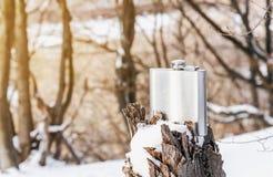 Metallic shiny flask for alcohol on a broken tree stump. Nature, winter, rest. Metallic shiny flask for alcohol on broken tree stump. Nature, winter, rest royalty free stock image