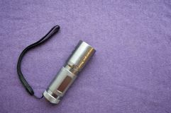 A metallic, shiny, made of stainless steel LED hand flashlight. With a cord on a purple background royalty free stock photos