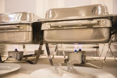 Metallic shiny trays are heated on gas burners royalty free stock photography