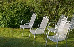 Metallic silver chairs in park on grass. In the background are bushes Royalty Free Stock Image