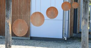Metallic sound disks hang on wires outdoors